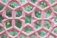 Seamless fence pattern. Abstract seamless star pattern in pink tone. Structure of geometric seamless star pattern of sandstone or stucco fence with green trees Stock Image