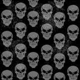 Seamless grunge pattern of gray grinning skulls Stock Photos