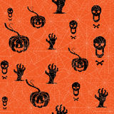 Seamless Halloween background. Pumpkin, skull and contorted hands on an orange backdrop with spider web. Stock Photo