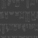 Seamless illustration  on the theme of washing and cleanliness, various clothes , a light contour icons on dark background. Seamless pattern on the theme of Royalty Free Stock Images