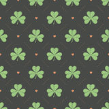 Seamless irish green pattern with clover and heart on a dark gray background stock illustration