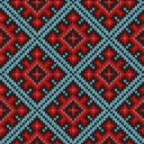 Seamless knitted pattern mainly in red and blue hues. Knitted geometric motley background mainly in red and blue hues, seamless knitting vector pattern as a Royalty Free Stock Image