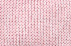 Knitted wool scarf fabric texture background. Seamless knitted pink and white wool scarf background. Neutral winter fabric  texture Royalty Free Stock Photo