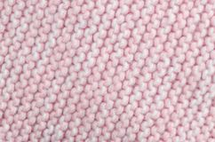 Knitted wool scarf fabric texture background. Seamless knitted pink and white wool scarf background. Neutral winter fabric  texture Royalty Free Stock Photos