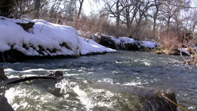 (Seamless Loop) Loop Seamless Snowmelt Stream Flowing. The snowmelt overflows the banks of the stream with its smooth current stock video