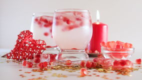 Seamless loop of romantic still life. Saint valentine`s day celebration. Two glasses with alcoholic cocktail and ice, decorated. Seamless loop of romantic still stock video