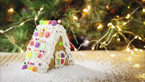 Seamless loopable snow on Gingerbread house with Christmas tree background. Holiday concept. Cinemagraph