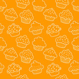 Seamless outlined cupcakes. Outlined cupcakes on orange Stock Photos