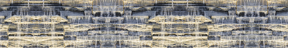 Seamless panoramic dark background of waterfall on stone wall. Seamless panoramic dark background of waterfall against stone wall texture with night backlit Royalty Free Stock Images