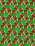 Seamless pattern of american football balls on the grass Royalty Free Stock Images