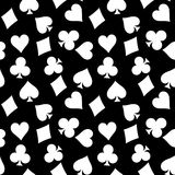 Seamless pattern background of white poker suits - hearts, clubs, spades and diamonds - on black background. Casino Royalty Free Stock Photo