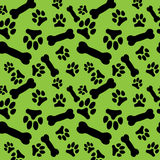 Seamless pattern with black dog paw prints and bones on a green background Stock Image