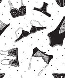 Seamless pattern of black icons of women's underwear on a white background with dots. Stock Photography