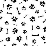 Seamless pattern of black paw prints and bones. Royalty Free Stock Photos