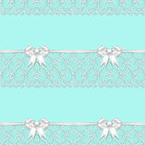 SEAMLESS PATTERN BLUE BACKGROUND DECORATED WITH WHITE LACE AND RIBBONS Stock Photo
