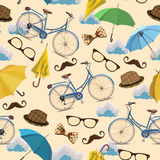 Seamless pattern with blue vintage bicycles, glasses, umbrellas, clouds, bows, hats, mustache on beige background. Stock Image