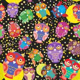 Seamless pattern bright colorful cute owls on black background, funny birds face with winking eye, bright colors. Vector. Illustration Stock Photography
