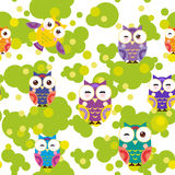 Seamless pattern - bright colorful owls and green leaves on white background. Vector Stock Images