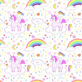 Seamless pattern with bright cute unicorns and rainbows. Stock Images