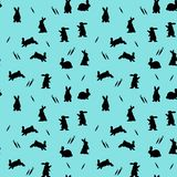Seamless pattern, bunnies on a light blue background, and carrot. Silhouette vector Stock Photography