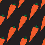 Seamless pattern with carrots on the black background Stock Images