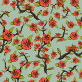 Seamless pattern of cherry blossoms. Abstract bright orange flowers on a branch with leaves on a pale green background. Vector illustration Royalty Free Stock Photography
