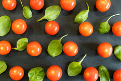 Seamless pattern with cherry tomatoes and spinach. Abstract background. Tomato the black background. Group of red ripe Royalty Free Stock Photo