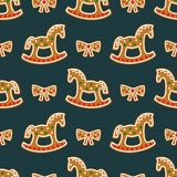 Seamless pattern with Christmas gingerbread cookies - rocking horses and bows. Winter holiday vector design illustration Stock Photos