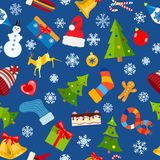 Seamless pattern of Christmas symbols. And warm winter clothes in flat style on blue background Royalty Free Stock Photos