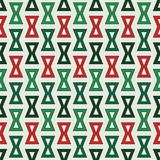 Seamless pattern in Christmas traditional colors with repeated hourglass. Ethic and tribal motif. Geometric background Stock Image