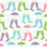 Seamless pattern with colored rubber boots and umbrellas under r Stock Images