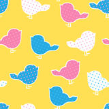 Seamless pattern with colorful birds silhouettes on yellow back. Ground. Birds in polka dots Stock Photos
