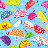 Seamless pattern with colorful umbrellas. On blue background Royalty Free Stock Image