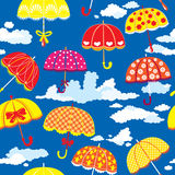 Seamless pattern with colorful umbrellas and cloud. S on blue background Stock Image