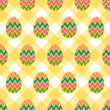 Seamless pattern of easter eggs with colorful zigzag patterns. Seamless pattern of colorful wavy eggs on a tablecloth background with pastel yellow subtle look Stock Photo