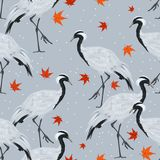 Seamless pattern with cranes and maple leaves vector illustration