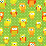 Seamless pattern with cute cartoon owls on green dotted background. Royalty Free Stock Photography