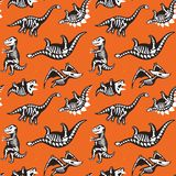 Seamless pattern with cute scary silhouettes of dinosaurs with a skeleton. Halloween Holidays orange background. Seamless pattern with cute cartoon silhouettes Stock Photography