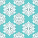 Seamless pattern of cutout paper abstract lacy snowflakes on blue background. Stock Image