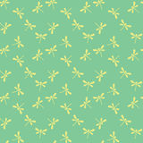 Seamless pattern with dragonflies. Vector seamless green pattern with yellow silhouette dragonflies Royalty Free Stock Photo