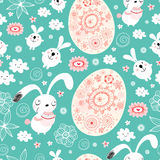 Seamless pattern of Easter bunnies and eggs. Seamless pattern of funny bunnies and Easter eggs on a blue background