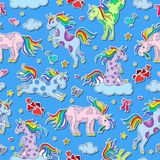 Seamless illustration  with funny cartoon unicorns, hearts and stars color sticker icons on blue  background. Seamless pattern with funny cartoon unicorns Stock Photo