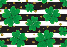 Seamless pattern with green clover leaves, gold gitter textured polka dots, stripes. Stock Photography