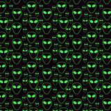 Seamless pattern from the green head of the aliens.  Stock Photos