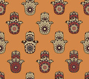 Seamless pattern with hamsa. Drawing of a seamless pattern with different hamsa on orange background Royalty Free Stock Photography