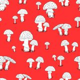 Seamless pattern with hand drawn mushrooms on the red background Stock Photos