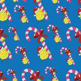 Seamless pattern with happy chicken in Santa hat and candy on blue. Christmas and New Year seamless background for greeting cards, posters, invitations Stock Image