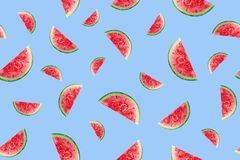 Seamless pattern of juicy watermelon slices on a blue background stock illustration