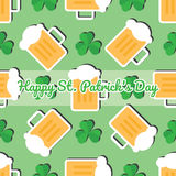Seamless pattern with leaves of the trefoil and mugs of beer on a green background Royalty Free Stock Image