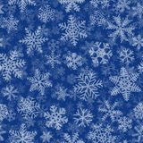 Seamless pattern of many layers of snowflakes. Christmas seamless pattern of many layers of snowflakes of different shapes, sizes and transparency. White on blue Stock Photo